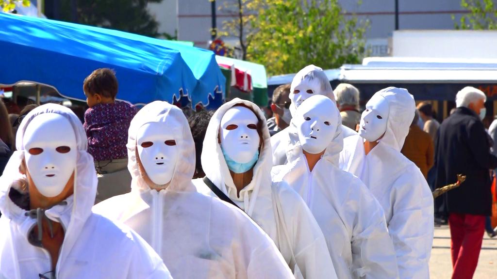 Les masques blancs déambulent au milieu du marché